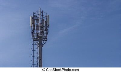 The tower with a staircase to the antennas of mobile phone communication, television, Internet, radio, on a background of blue sky. Birds sitting on the antennas of the tower