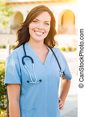 Portrait of Young Adult Female Doctor or Nurse Wearing Scrubs and Stethoscope Outside.