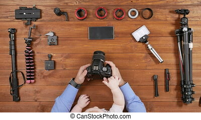 Photographer father with a young son checked the camera before shooting. Wooden table top view. Toddler touching a button. Equipment for shooting on the table.