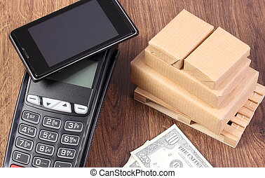 Payment terminal with mobile phone with NFC technology, currencies dollar and wrapped boxes on wooden pallet