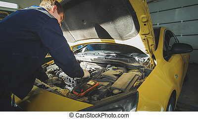 Mechanic caucasian in car service - repairing in engine...