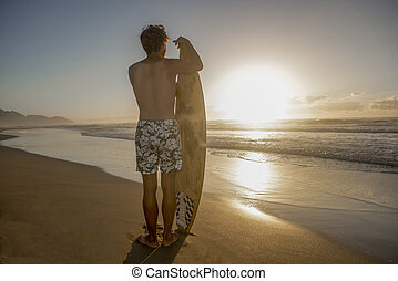 Young surfer on beach with voard at dawn - A young surfer...