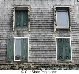 Four Windows with Decorative Shutters on an Old Gray House