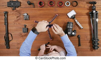 Photographer father with a young son make selfie phone. Wooden table top view. The kid plays with a brush for cleaning. Equipment for shooting on the table.