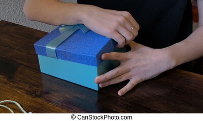 Young beautiful girl opens a box with gifts. The blue color...