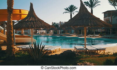 Sunny Hotel Resort with Blue Pool, Palm Trees and Sunbeds in...
