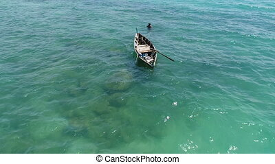 Sea, boat and fisherman in the water - Aerial view of boat...