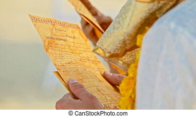 Closeup Golden Sheets with Vows in Newlyweds Hands -...