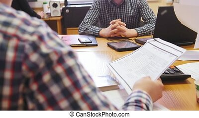 Office: Business people in meeting room discussing financial report using data and gadget