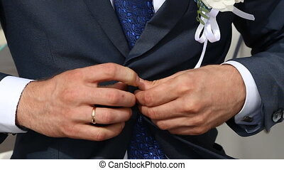 groom buttoned tuxedo and corrected then. man dressed in a...