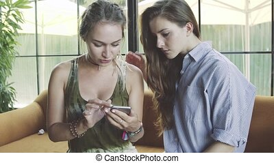 Two young girlfriends using smartphone and talking in cafe
