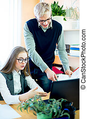 two employees at a laptop - young girl in glasses and the...