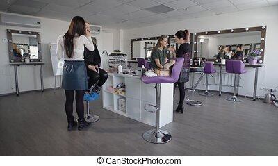 Two beginners make-up artists are trained to apply makeup professional cosmetics. As models have two girls, one blonde, the other with dark hair. In background, a lot of mirrors, where the model look