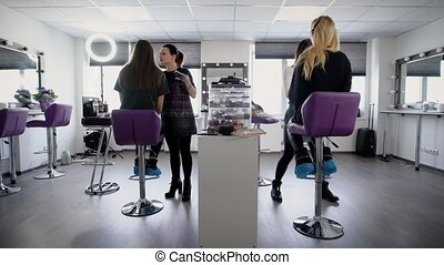 Students of college trying to make his first make-up on the practical training in professional beauty salon. Young girls learn a new profession in the fashion industry.