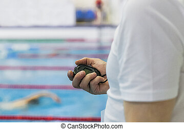 referee timekeeper with stopwatch in hand in swimming...