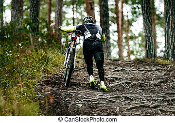 cyclist walk climbs uphill on dirt trail in forest