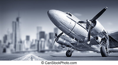 travel background - old airplane against a city skyline