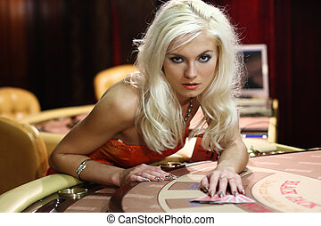 young women in casino takes playing cards