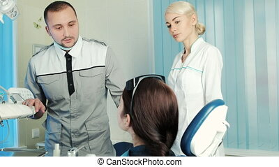 Dentist and his assistant listen carefully patient...