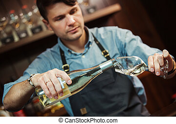 Male sommelier pouring white wine into long-stemmed...