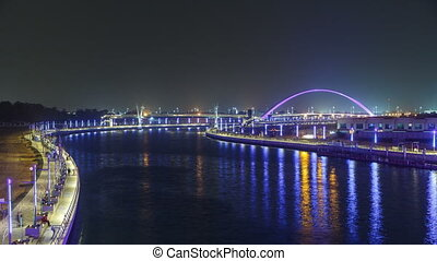 Two bridges over newly opened Dubai canal with a boat...