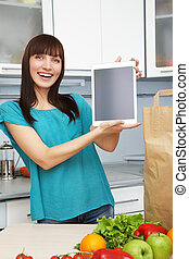 housewife uses a tablet computer in the kitchen - young...