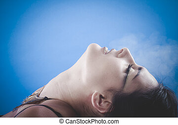Brunette woman with smoke coming out of her lips, concept...