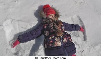 girl makes a butterfly in the snow, winter weather