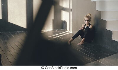 Young teenage girl actress with smudged makeup crying after loss film casting sitson floor in studio indoors