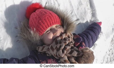 girl lying on white snow and laughing, happy winter