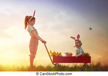 children wear bunny ears - Two cute little children wear...