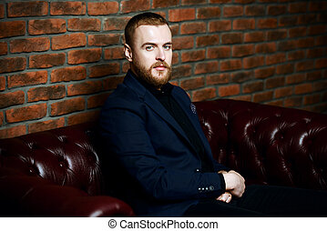 man on a sofa - Imposing well dressed man sitting on a...