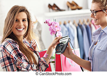 Female customer paying for clothes in boutique