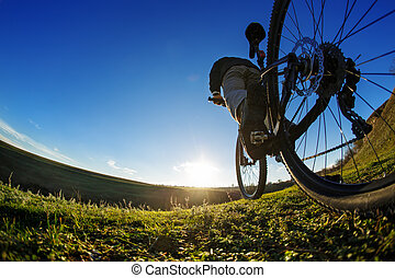 Riding a bike down a trail, close-up the rear wheel. Showing...