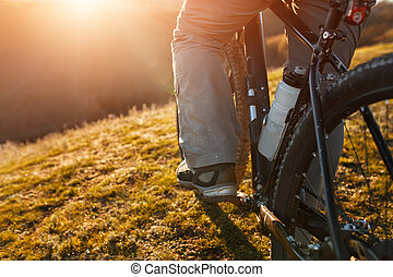 cyclist legs riding mountain bike on the hill in spring...