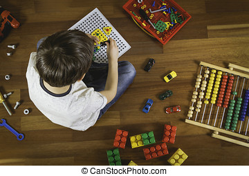 Child playing with toys while sitting on wooden floor. Top...