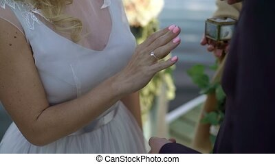 Groom puts on wedding ring to bride's hand outdoors