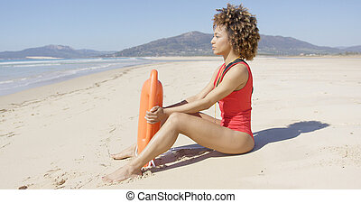 Lifeguard sitting with rescue float on beach - Female...
