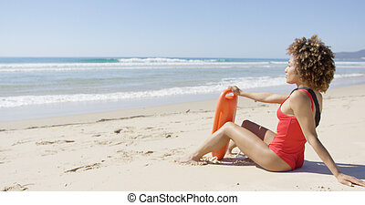 Female with rescue float sitting on beach - Female wearing...