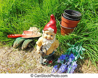 Garden gnome surrounded by grass and tools - Garden gnome...