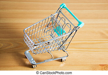 a shooping cart - a shopping cart on wooden background