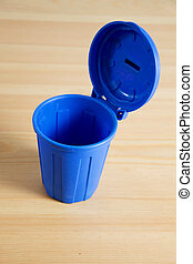 a blue garbage can on wooden background
