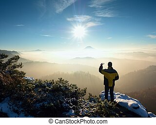 Photographer by smart phone takes picture of misty hilly...