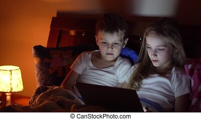 kids playing tablet in bed - cute kids playing tablet in bed