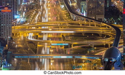Aerial view of highway junction with traffic timelapse in Dubai, UAE, at night. Famous Sheikh Zayed road in Dubai downtown.