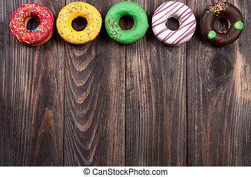 glazed donuts on a black wooden background with copy space...