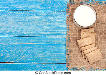 glass of milk with grain crispbreads on a blue wooden background with copy space for your text. Top view