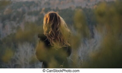 Brown-haired woman standing in winter landscape inside...