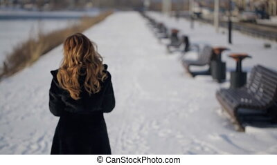 woman strolling along promenade on bank of river in winter....