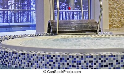 Jacuzzi among swimming pool with SPA. Relaxing in warm...